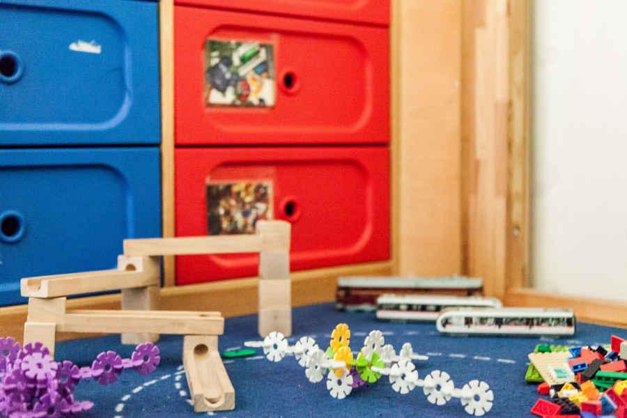 Auf dem Podest befindet sich die Bauecke mit unterschiedlichen Legosteinen, Zugschienen, Steckblumen, Fahrzeugen und Bausteinen.