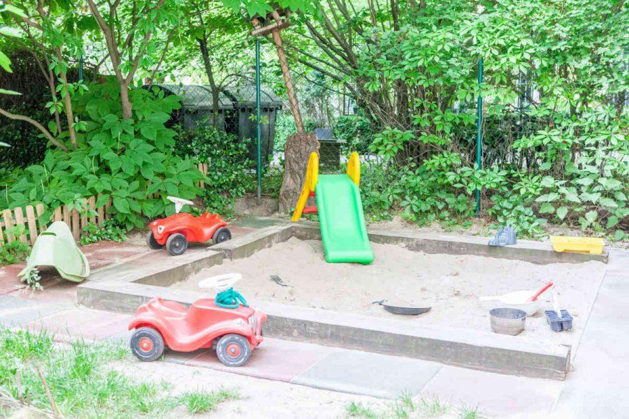 Im Innenhof befindet sich ein kleiner Sandkasten mit Wasseranschluss. Hier planschen und matschen die Kinder im Sommer