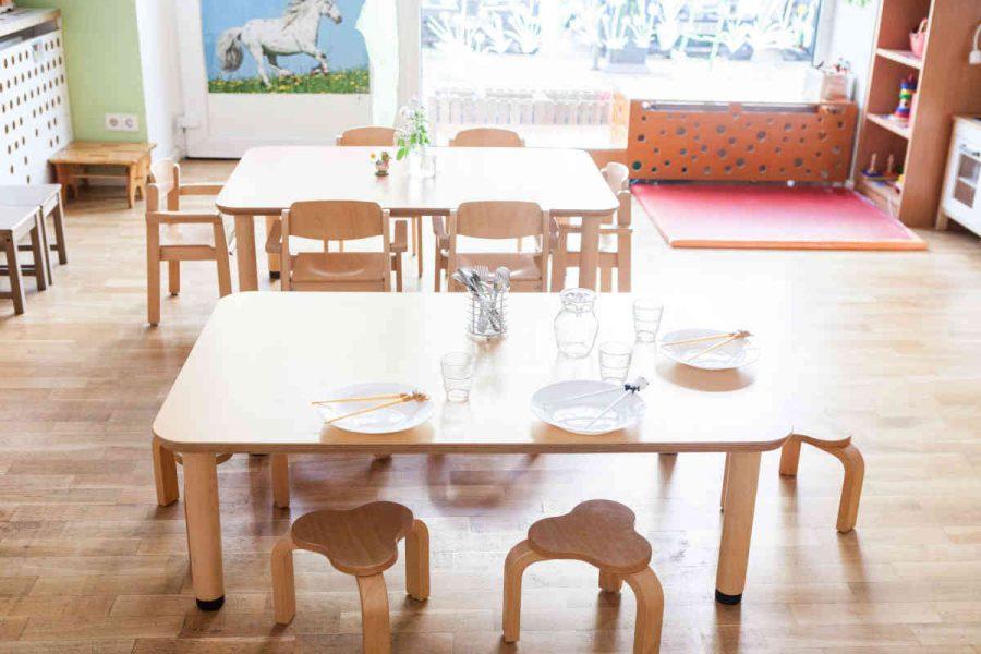 In kleinen Sitzgruppen essen die Kinder im Gruppenraum Mittagessen.